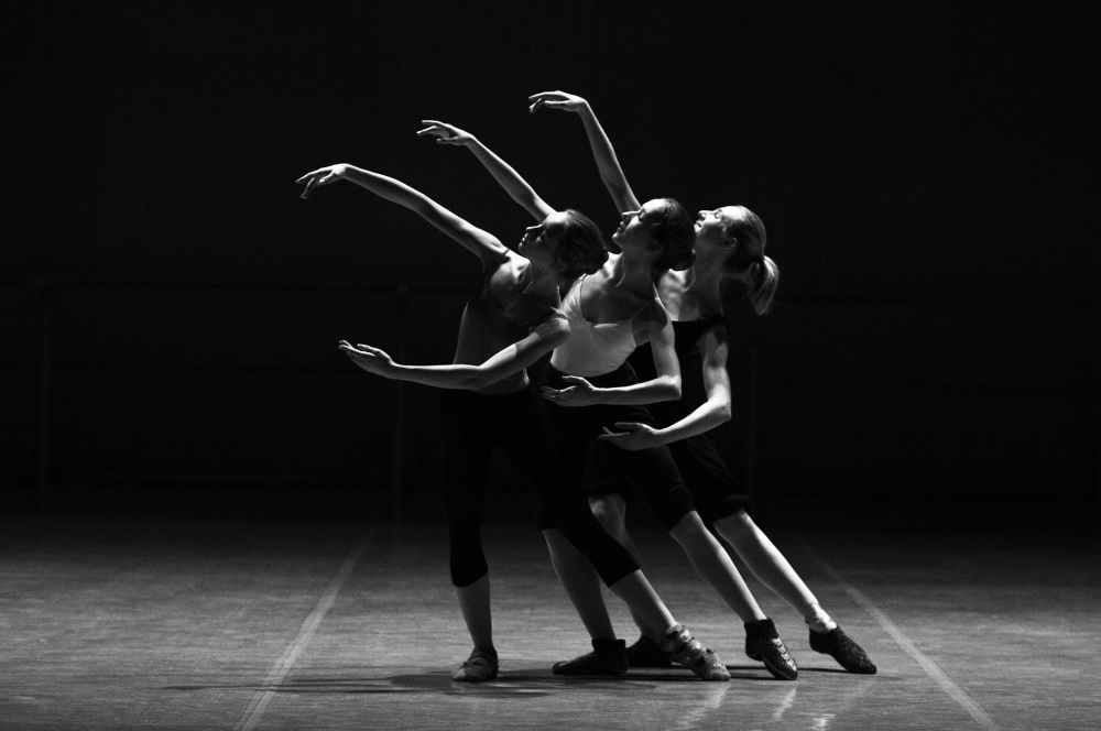 black and white photograph of three dancers on a stage